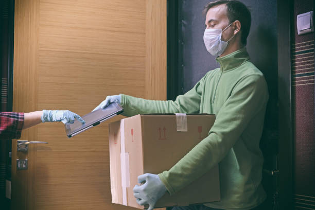 courier in protective mask delivers parcel to client, client in medical gloves signs on tablet. delivery service under quarantine, disease outbreak, coronavirus covid-19 pandemic conditions. - servizi essenziali foto e immagini stock