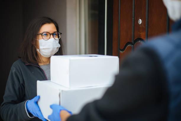 보호 마스크의 택배는 고객에게 소포를 배달합니다. 스톡 사진