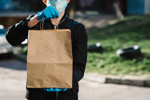 courier in protective mask, medical gloves delivers takeaway food.  employee hold cardboard package. place for text. delivery service under quarantine, 2019-ncov, pandemic coronavirus, covid-19. - delivery стоковые фото и изображения