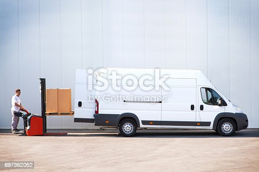 istock Courier is loading the van with parcels. 697362052