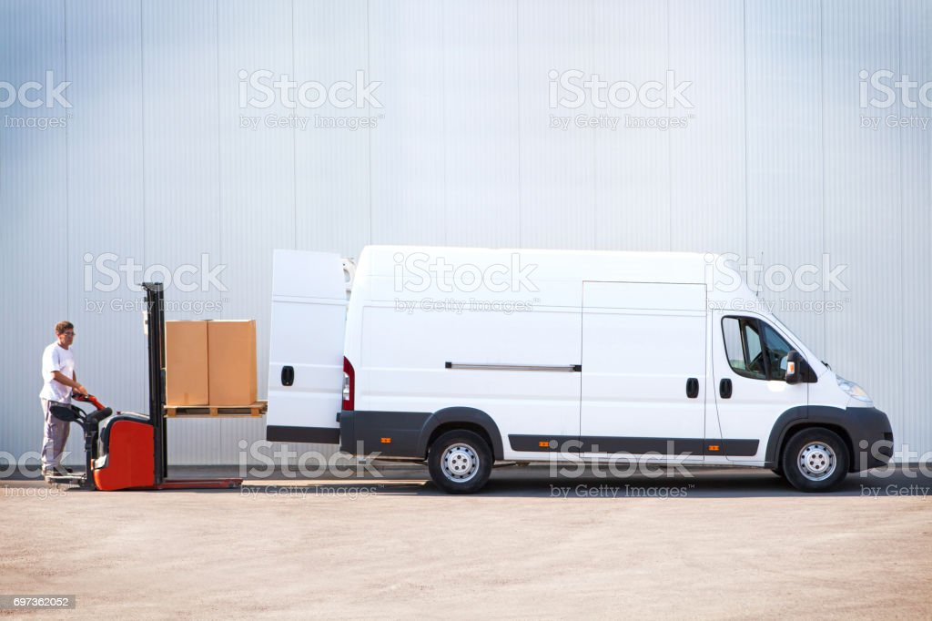 Courier is loading the van with parcels. stock photo