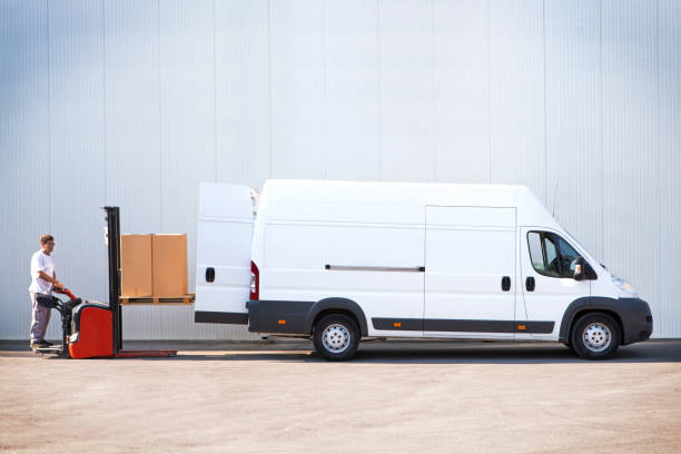 Courier is loading the van with parcels. Courier loading the parcels with forklift. commercial land vehicle stock pictures, royalty-free photos & images