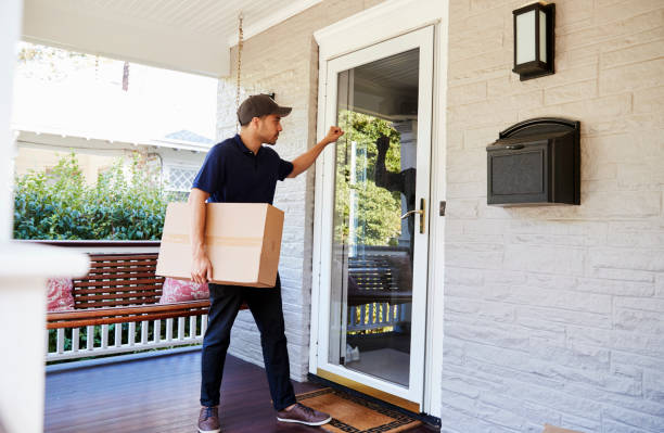 courier knocking on door of house to deliver package - addetto alle consegne foto e immagini stock