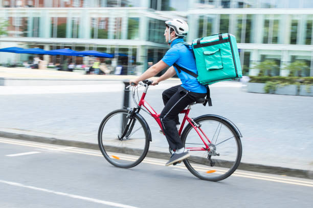 Courier On Bicycle Delivering Food In City Courier On Bicycle Delivering Food In City delivery man stock pictures, royalty-free photos & images