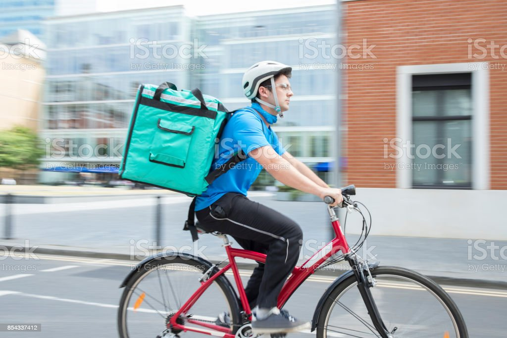 Courier On Bicycle Delivering Food In City stock photo