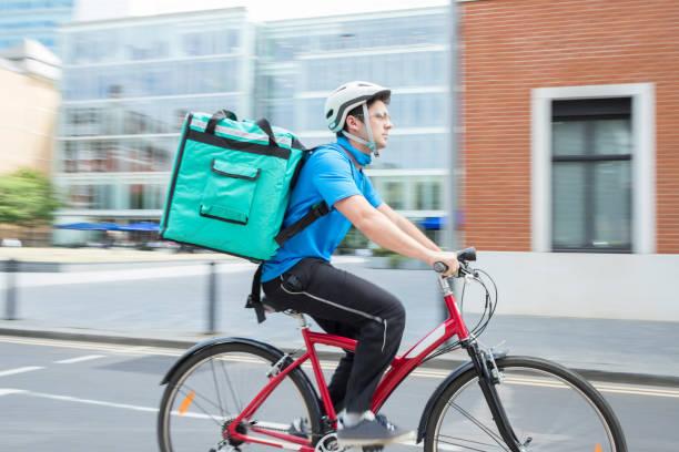 市内で食品を提供する自転車の宅配便 - 配達 ストックフォトと画像