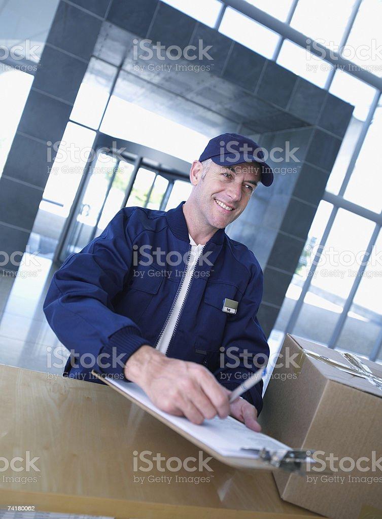 Courier com Prancheta e caixa de cartão foto de stock royalty-free
