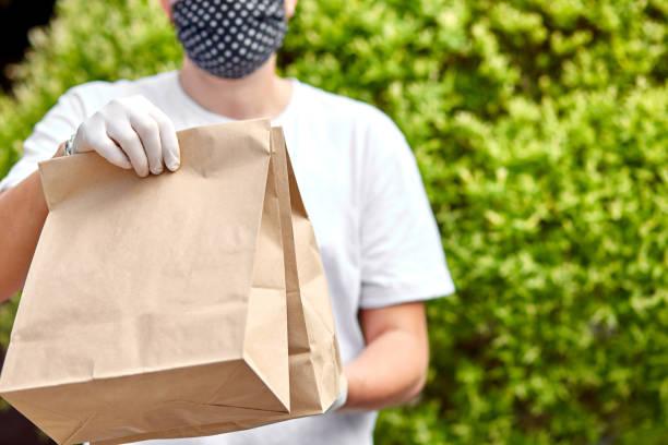 Courierin weiß halten Go Box Essen, Lieferservice, Takeaway Restaurants Essen Lieferung nach Hause Tür. Bleiben Sie zu Hause sicher Leben von Coronavirus COVID-19 Ausbruch. Kontaktloser Lieferservice unter Quarantäne. – Foto