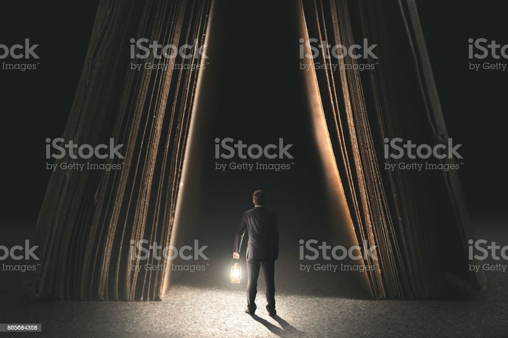couriose man with lamp going to be wise in a book stock photo