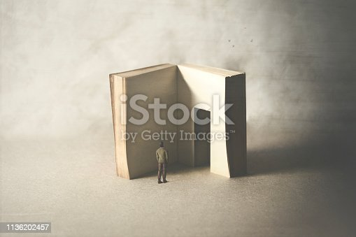 istock courious man entering in the book's door, fear of wisdom 1136202457