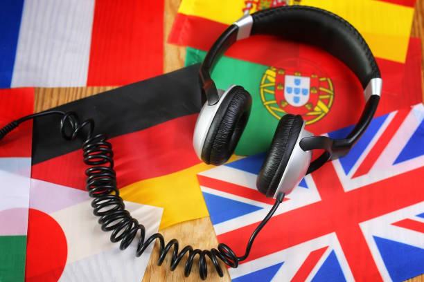 kurs sprache kopfhörer und flagge auf einem tisch - spanisch translator stock-fotos und bilder