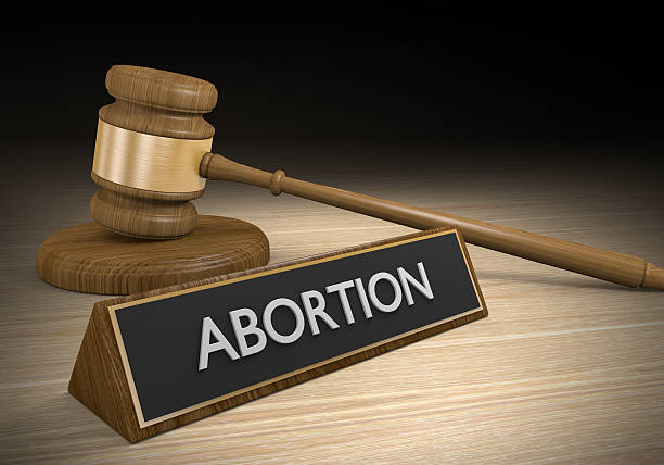 Court legal concept of abortion law A wooden court gavel next to a sign that says abortion on it. pro choice stock pictures, royalty-free photos & images