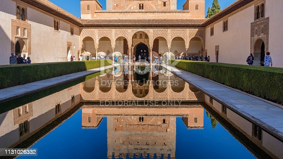Granada, Spain - October 25, 2018: The Court of the Myrtles is part of the palace and fortress complex of the Alhambra. It is also called Mirtos, Arrayanes or Alberca courtyard. The Court of the Myrtles south portico and Tower of Comares are reflected in the central pool.