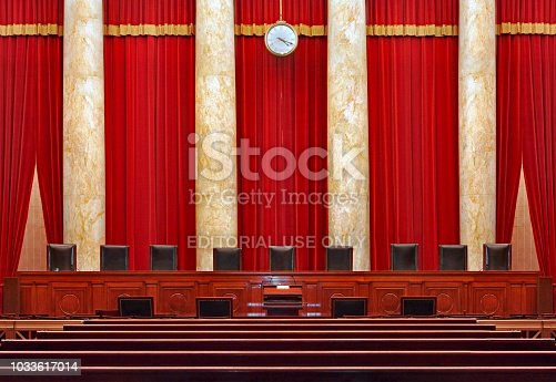 Washington, DC, USA - June 9, 2014:  The seats for the nine powerful judges of the Supreme Court face the courtroom against a red backdrop.