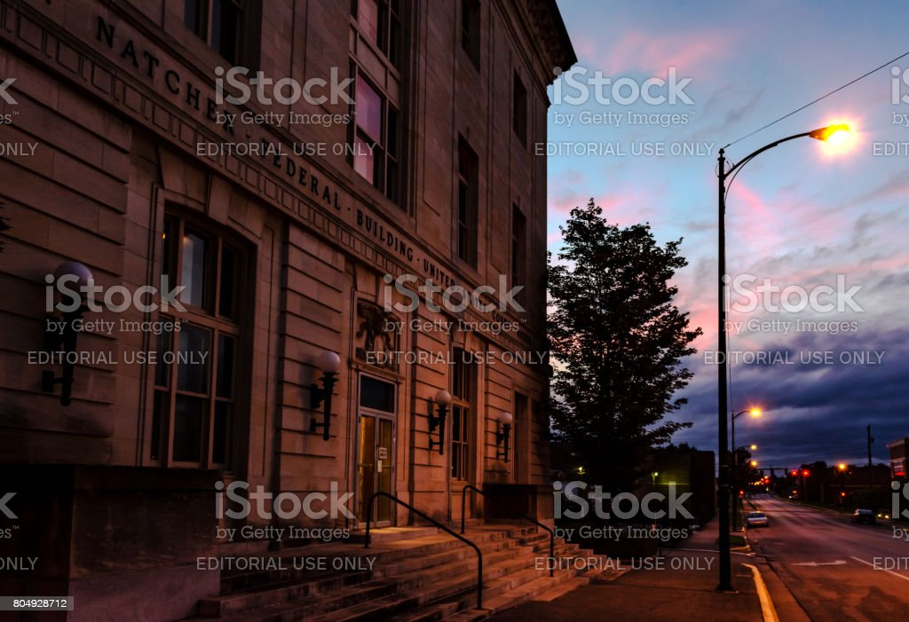 Courthouse lit by a streetlamp at blue hour stock photo