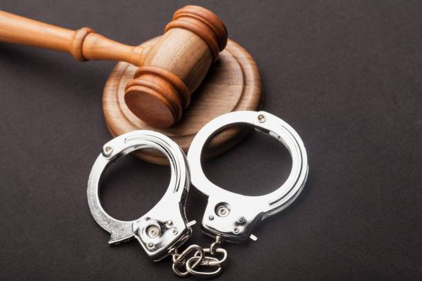 Courtroom. High Angle View Of Judge Gavel And Handcuffs On Wooden Desk criminal stock pictures, royalty-free photos & images
