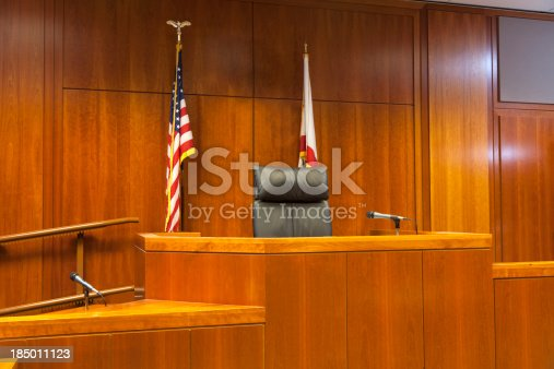 A witness stand and judges bench in an American courtroom.