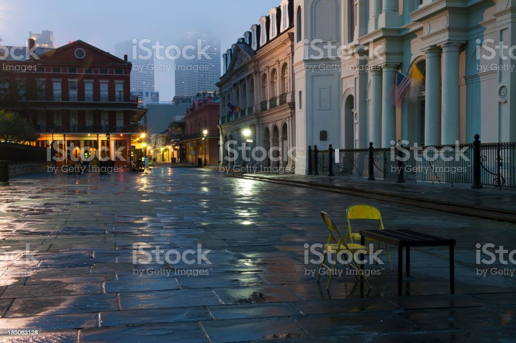 A courtyard at dusk with a card table and two yellow chairs stock photo