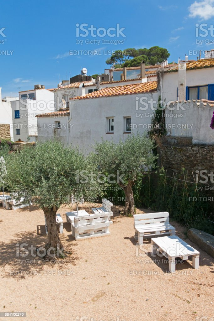 Courtyard with seating and olive trees, in the small fishing town of cadaques, Catalonia, Spain stock photo
