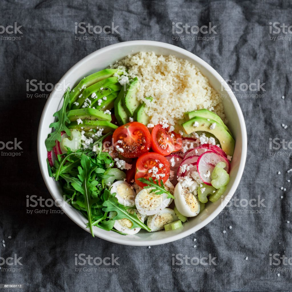 Couscous and fresh vegetables buddha bowl. Healthy, diet,  food concept. Cous cous, quail eggs, tomatoes, radish, arugula, avocado bowl on gray background, top view stock photo