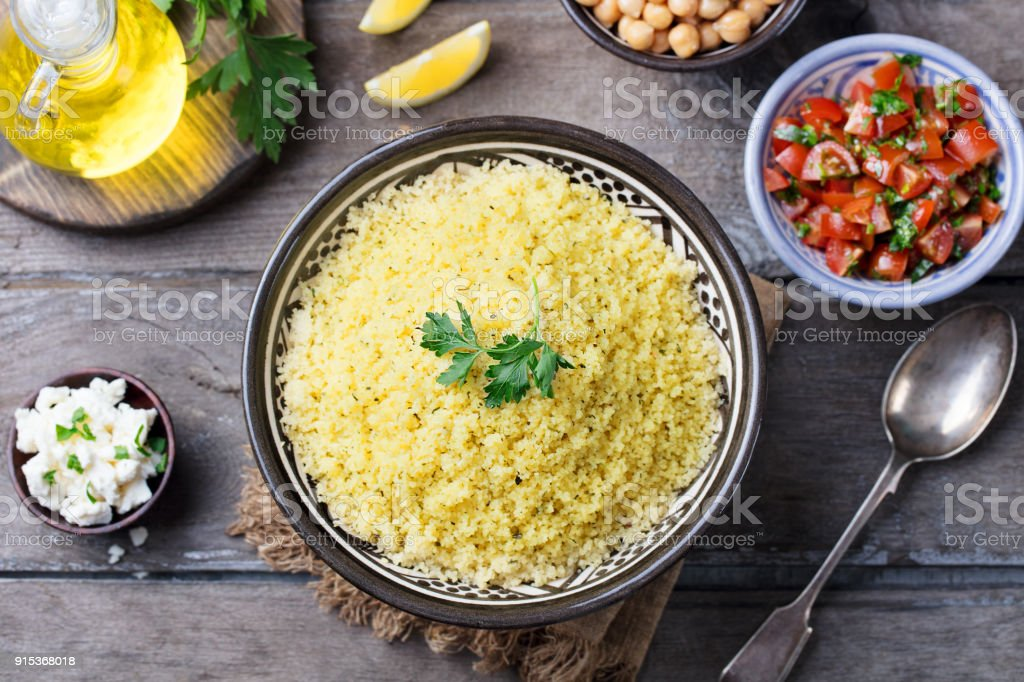 Couscous in bowl. Wooden background. Top view. stock photo