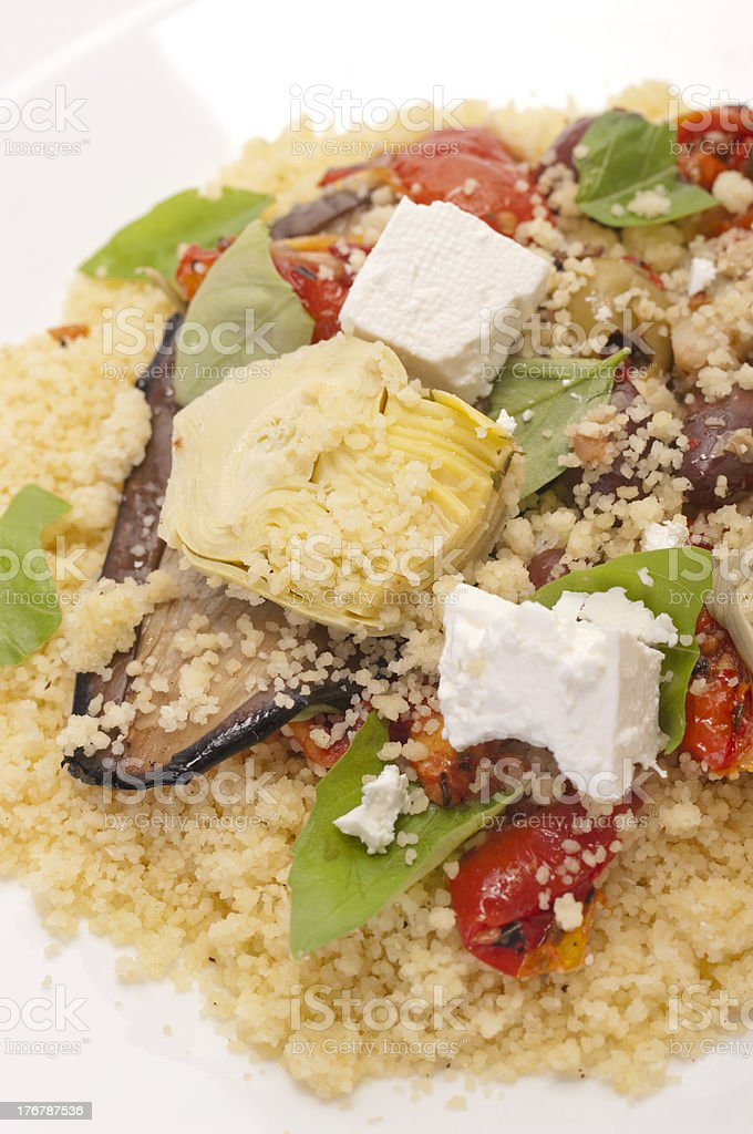 Couscous with antipasto vegetables, fetta cheese and basil stock photo