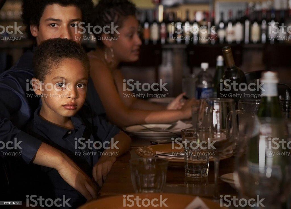 Cousins dining with family at restaurant royaltyfri bildbanksbilder