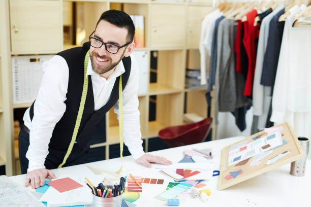 Couturier at workplace Happy clothier standing by his workplace in studio of fashion fashion designer stock pictures, royalty-free photos & images