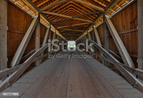 The wooden supporting architecture of covered bridge is viewed from the inside. This is Parke County, Indiana's Sanitorium Covered Bridge.