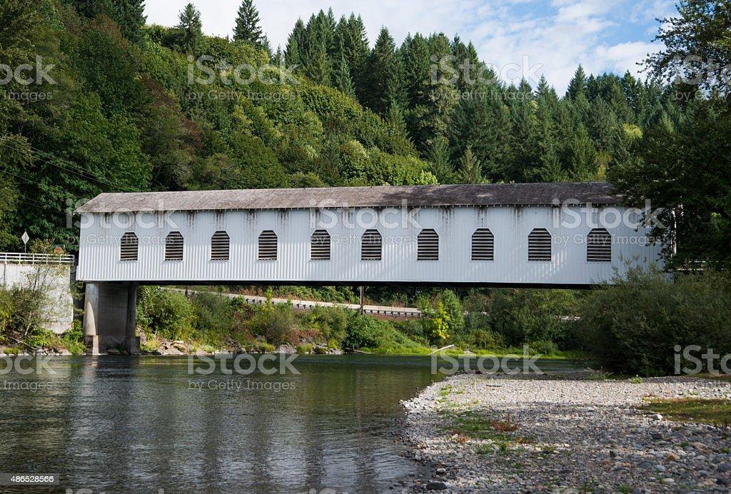 Covered bridge over river stock photo