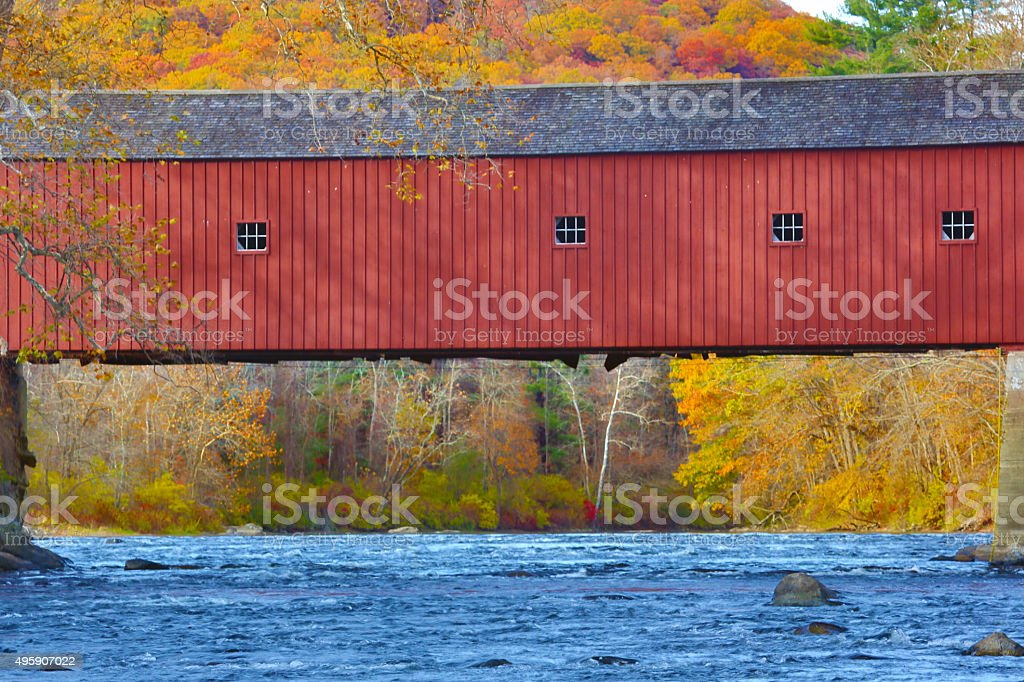 Covered bridge with fall foliage and blue water, western Connect stock photo