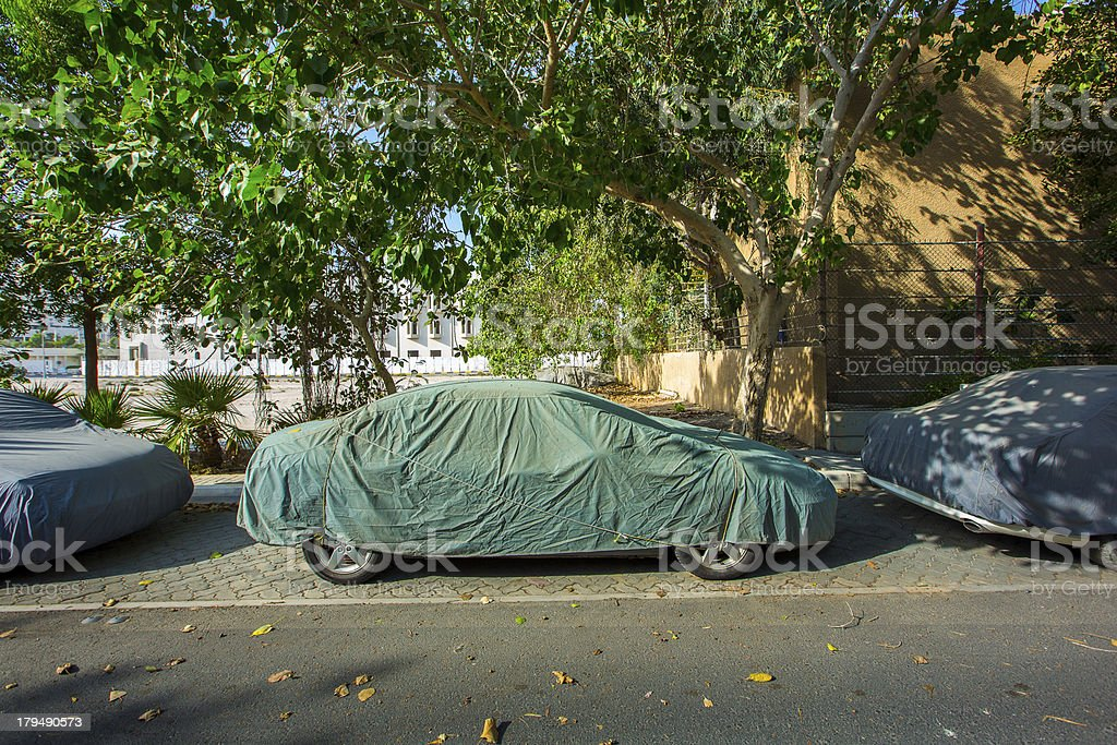 Covered Car Side view Under the Tree. A sedan type car covered with a...