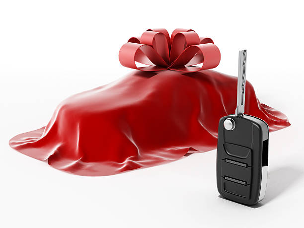 covered car wrapped with ribbon and car key - autoschleifen stock-fotos und bilder