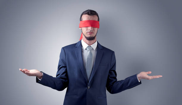 Covered eye businessman in front of a wall stock photo