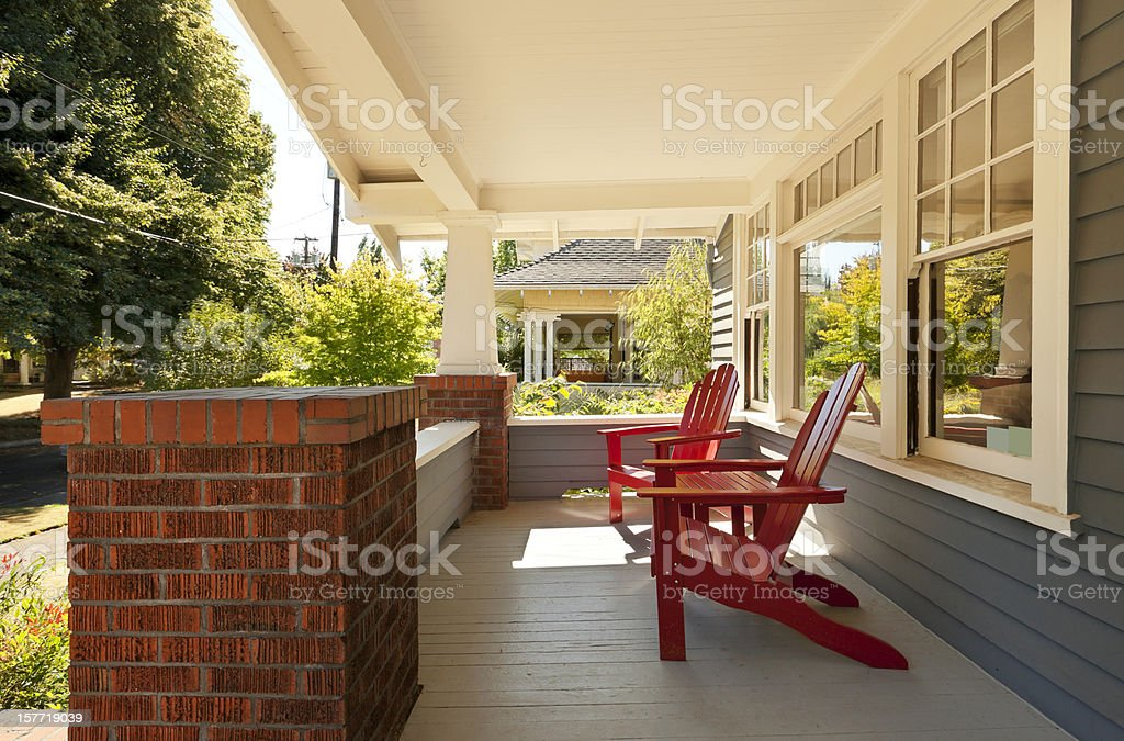 Covered front porch with two red wood chairs stock photo