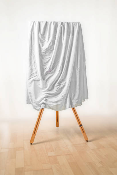 covered painting on an easel, white cloth over the picture, wooden floor and light background, art concept for an exhibition opening day or a presentation ceremony, copy space - covering stock photos and pictures