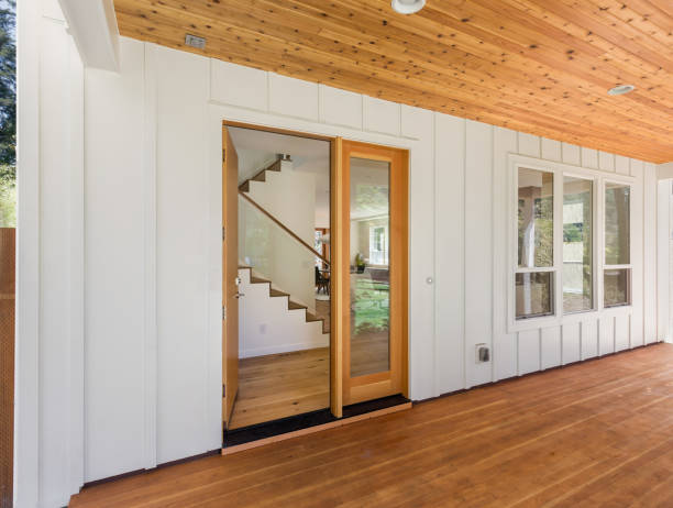 Covered porch and front door of beautiful new home. Features white siding and rich warm wood porch and ceiling. Door is open. stock photo
