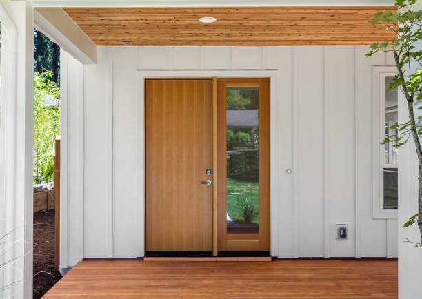 Covered porch and front door of beautiful new home. Features white siding and rich warm wood porch and ceiling. Door is closed. stock photo