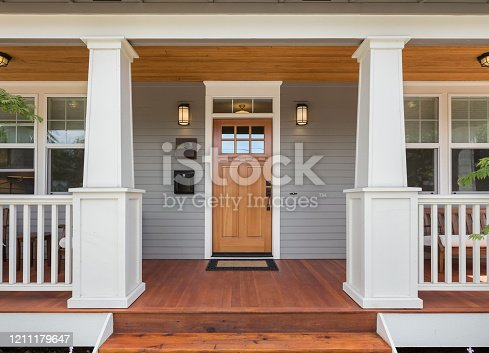 istock Covered porch and front door of beautiful new home 1211179647