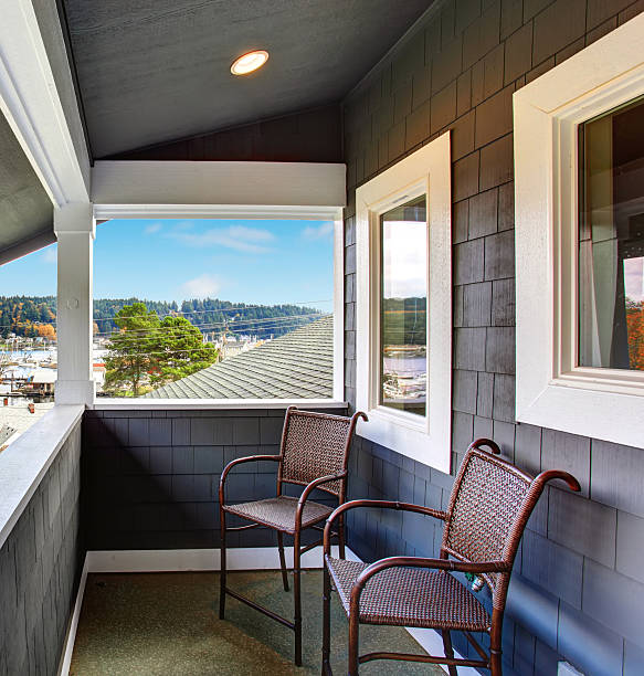 Covered porch of the blue siding home with two chairs. Covered small porch of dark blue Northwest home in Gig Harbor. gig harbor stock pictures, royalty-free photos & images