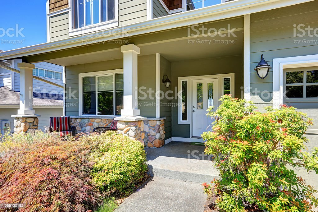 Covered porch with white columns and stone trim. stock photo