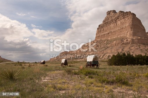 With yuccas and prairie in the foreground, clouds pass over old covered Conestoga and Murphy Wagons on the Oregon Trail with Scotts Bluff in the background in Scotts Bluff National Monument in Nebraska.
