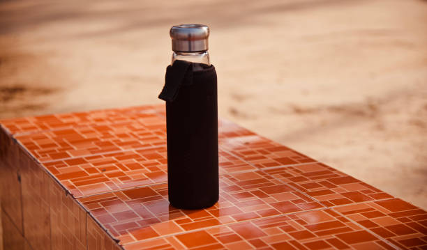 A covered water bottle on a tiles surface stock photo