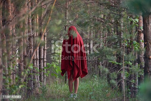 Woman under red fabric standing mystically in solitary green woods on empty alley