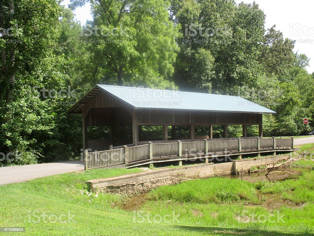 Covered Wooden Bridge Over River in Park stock photo