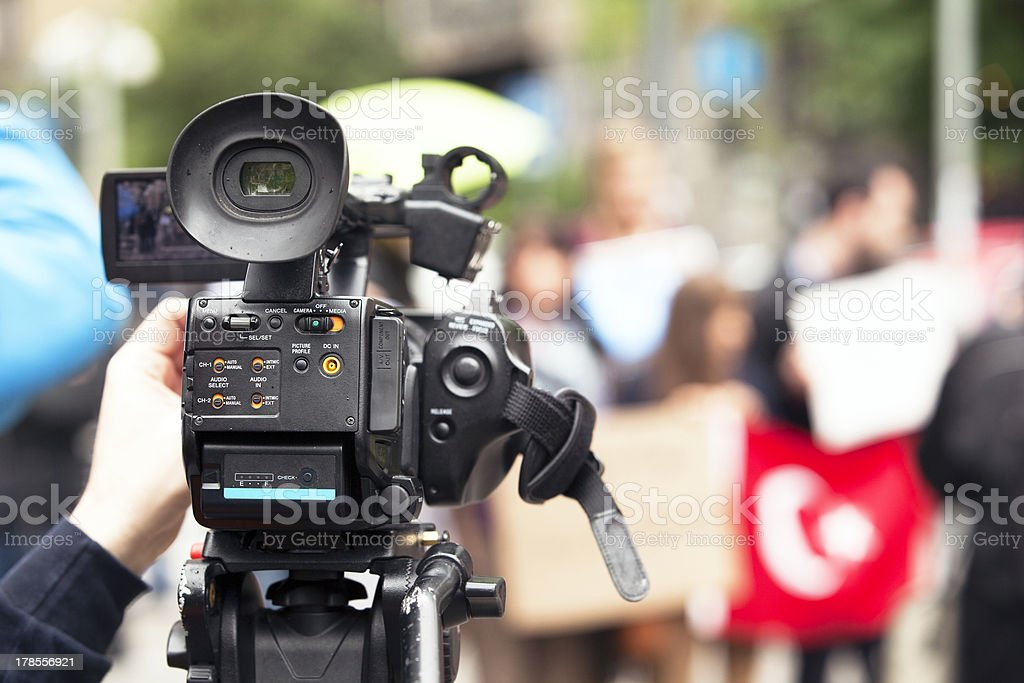 Covering a street protest using video camera royalty-free stock photo