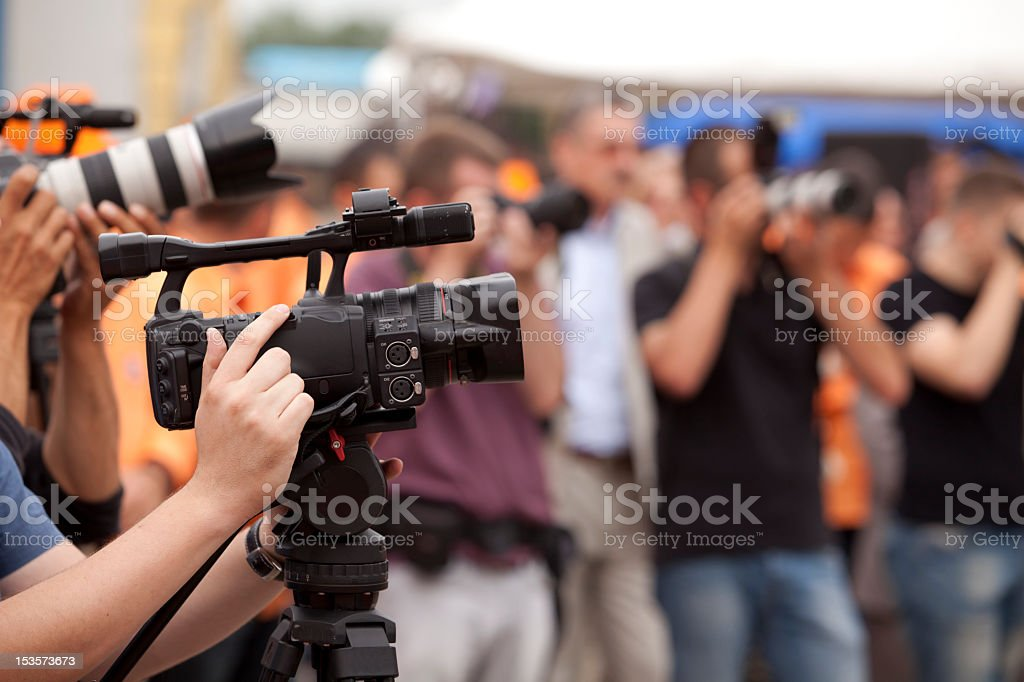 Covering an event with a black video camera royalty-free stock photo