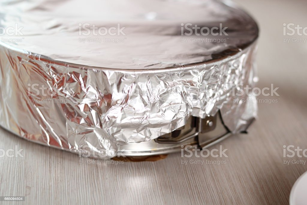 Covering baking pan with foil before and place to fridge. Making frozen strawberry cheesecake series. royalty-free stock photo