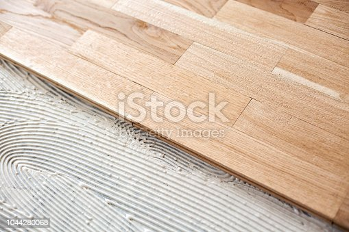922081754istockphoto Covering of a floor with parquet 1044280068