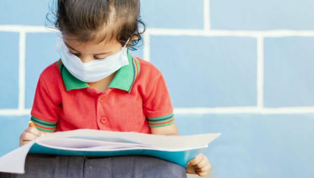 covid 19 ou coronavirus et pollution de l'air pm2.5 concept - petite fille portant un masque médical et occupé à écrire à l'école - montrant wuhan covid-19 ou sars cov 19 épidémie ou épidémie de virus. - masque enfant photos et images de collection